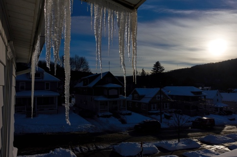 Icicles hanging from roof with sun shining through clouds